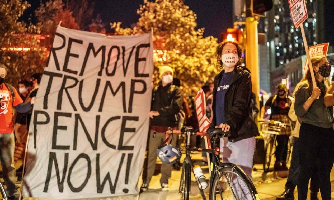 """Pessoas seguram uma placa """"Remova Trump Pence já"""" durante um protesto contra o racismo e as questões com a eleição presidencial em Minneapolis, Minnesota Foto: KEREM YUCEL / AFP"""