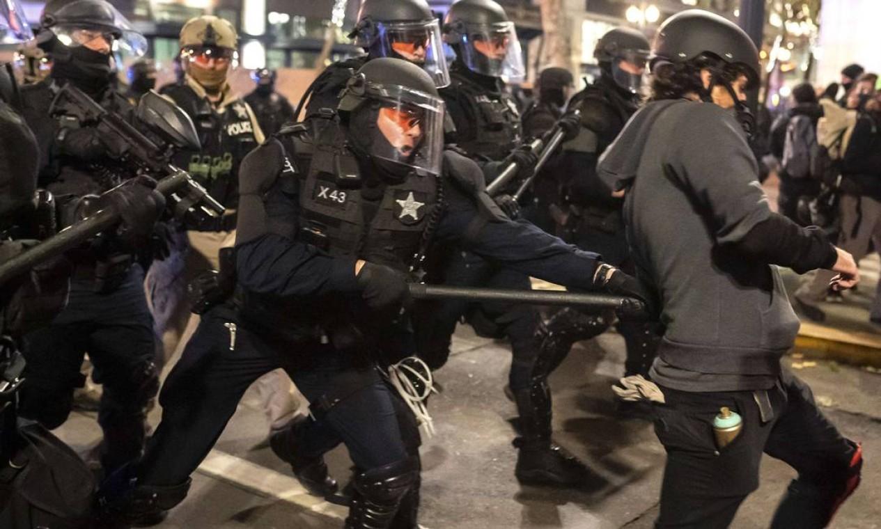 Tropa de choque atinge manifestante com bastão enquanto dispersa uma multidão de manifestantes do Black Bloc em Portland, Oregon Foto: Nathan Howard / AFP