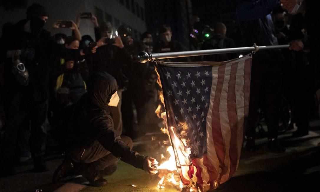 Manifestantes do Black Bloc queimam uma bandeira dos EUA em Portland, Oregon Foto: Nathan Howard / AFP