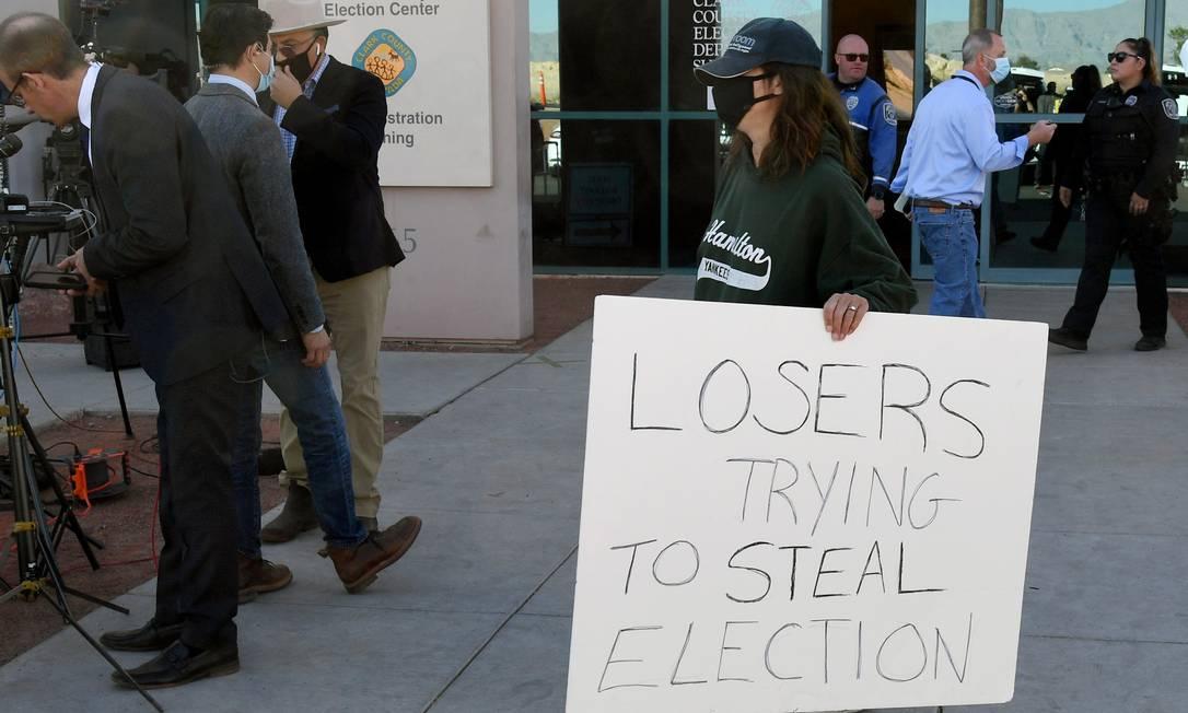 """Manifestante do lado de fora de local de votação em Las Vegas, com cartaz dizendo """"perdedores tentando roubar a eleição"""" Foto: Ethan Miller / AFP"""