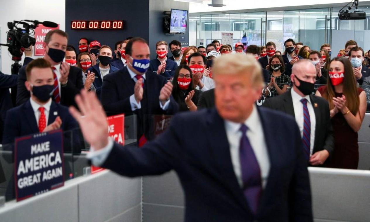 """A equipe de campanha de Donald Trump o aplaude durante visita à sede de campanha, no dia da eleição, em Arlington, Virgínia. """"Eu moro na mesma rua da sede da campanha de Trump, mas nunca tinha percebido quem trabalhava lá. Quando inesperadamente recebemos permissão para entrar no escritório, fiquei impressionado com a multidão de jovens bem vestidos atrás da campanha de reeleição do presidente - tensa, cansada e animada. Meio-dia, mas o relógio na parede havia parado depois de contar até a meia-noite"""". Foto: TOM BRENNER / REUTERS"""