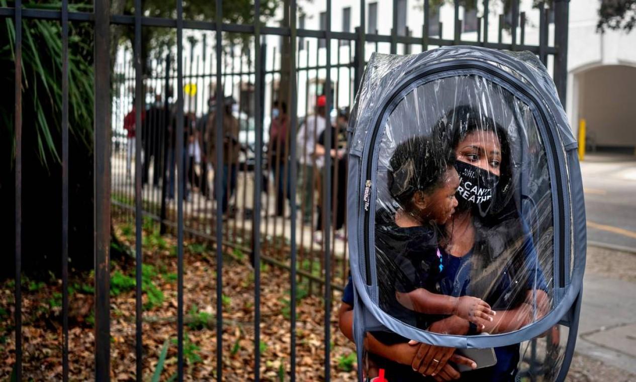 """Dana Clark e seu filho Mason, de 18 meses, esperam na fila conforme começa a votação antecipada em Nova Orleans, Louisiana. """"A professora Dana Clark estava ajustando uma 'cápsula de segurança' sobre ela e seu filho quando passei pela fila de votação em 16 de outubro, primeiro dia de votação antecipada em Nova Orleans. Ela comprou a cápsula para usar na sala de aula com seus alunos, na esperança de protegê-los, bem como seus próprios filhos e seu marido, da Covid-19. A imagem parecia expressar uma convergência de emoções amplamente sentidas: medo de contágio, esperança de um futuro da criança, pressões sobre os educadores e um desejo de justiça racial"""". Foto: KATHLEEN FLYNN / REUTERS"""