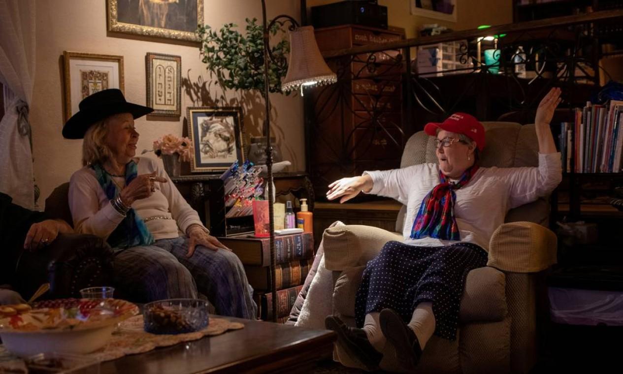 """Mayme Royer, 93, e Peggy Thornsburg reagem aos resultados da eleição durante uma festa pró-republicana no Texas. """"Encontrei um amigo de Peggy Thornsburg um dia antes da eleição, em Marfa, uma pequena cidade texana conhecida por sua cena artística ativa e luzes misteriosas que podem ser vistas disparando pelo deserto próximo. Peggy e seu marido, Kim, me convidaram para sua festa de vigia eleitoral. Este é o momento em que Thornsburg e sua amiga Mayme Royer, 93, se mexem e dançam em suas cadeiras para dizer que Trump está liderando a contagem na Flórida com a nova televisão de 74 polegadas que compraram para a ocasião"""". Foto: ADREES LATIF / REUTERS"""