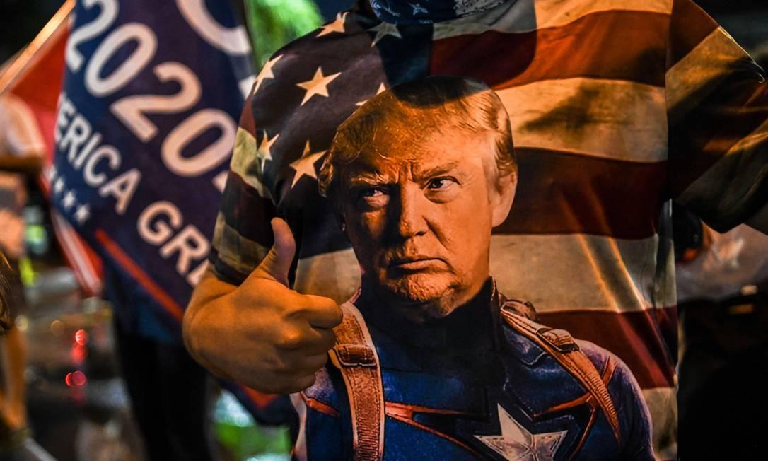 Apoiador de Donald Trump usa camiseta com o presidente vestido como o Capitão América, durante protesto em Miami Foto: CHANDAN KHANNA / AFP