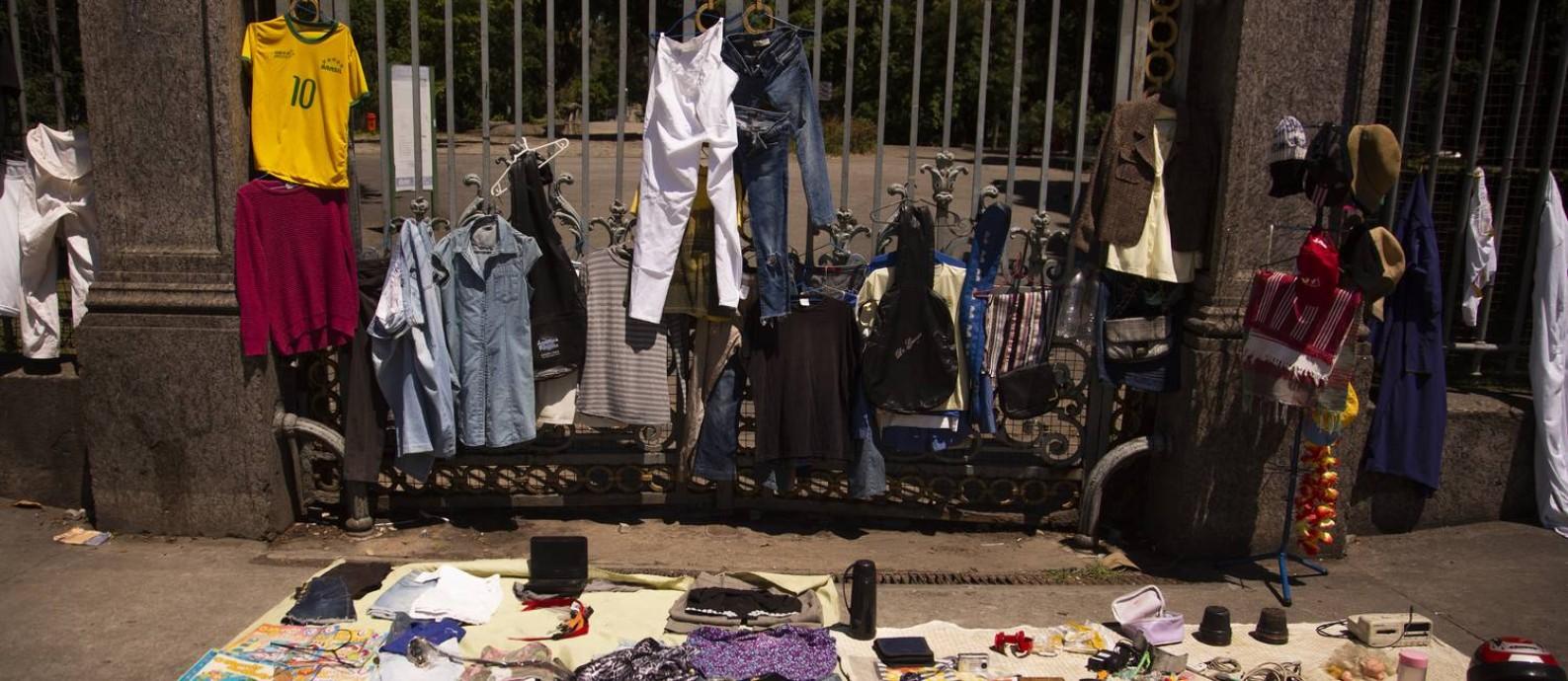 Roupas penduradas no gradil do Campo de Santana e outros itens à venda: carioca faz o que pode para minimizar os impactos do desemprego Foto: Gabriel Monteiro/Agência O Globo