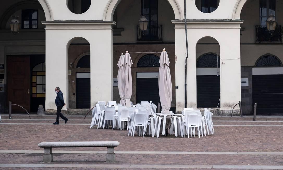 Homem usando uma máscara facial caminha perto de um bar fechado na Piazza Castello, em Torino, Itália. As novas medidas para conter a pandemia incluem bloqueio nas regiões de Valle D'Aosta, Piemonte, Lombardia e Calábria Foto: MARCO BERTORELLO / AFP