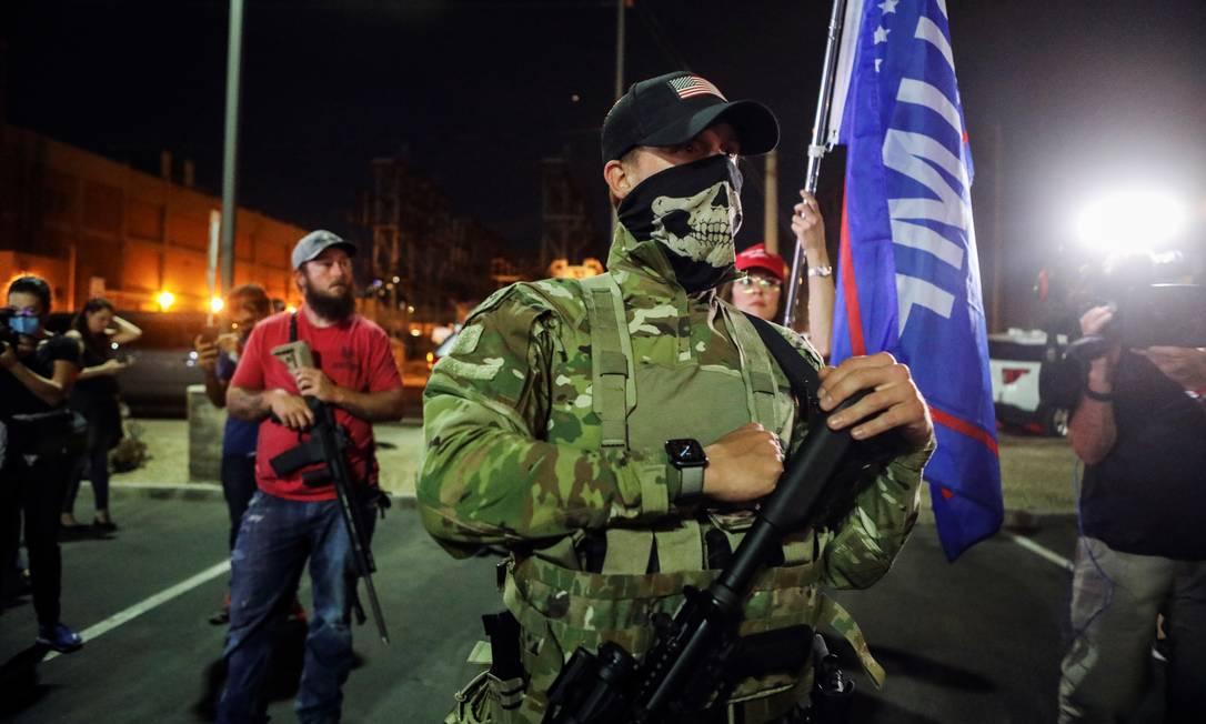 Apoiadores do presidente Donald Trump carregam rifles semiautomáticos enquanto protestam contra os primeiros resultados das eleições, em frente ao Centro de Tabulação e Eleição do Condado de Maricopa, em Phoenix, Arizona Foto: JIM URQUHART / REUTERS