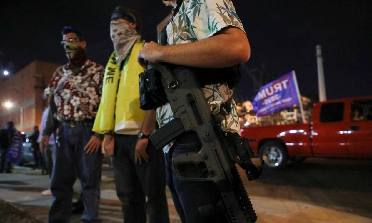 Armado com um rifle, um apoiador do presidente Trump participa de protesto em frente ao local de contagem de votos no Arizona, onde Joe Biden abriu vantagem em relação a presidente Foto: JIM URQUHART / REUTERS