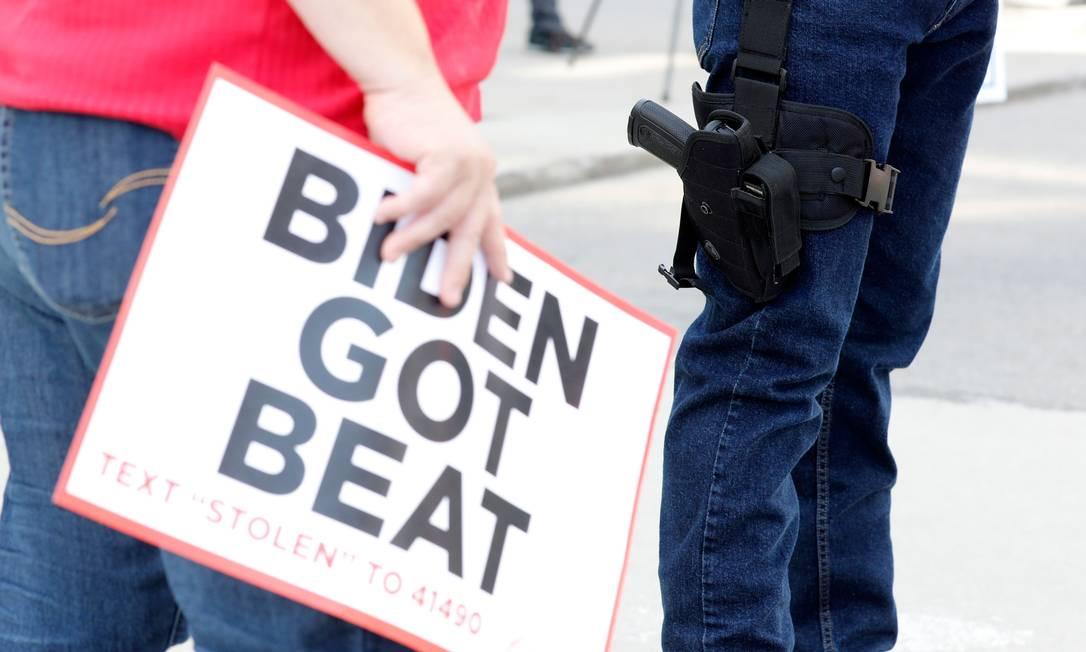 """Um apoiador de Trump carrega uma arma fora do TCF Center, em Detroit, enquanto outro exibe um cartaz com a frase """"Biden foi derrotado"""" Foto: JEFF KOWALSKY / AFP"""