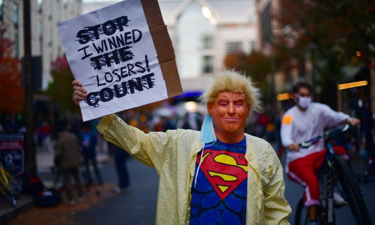 """Ativista vestido como o presidente Donald Trump e com uma camisa do Superman exibe um cartaz com a frase """"Ganhei, perdedores!"""" Foto: MARK MAKELA / REUTERS"""