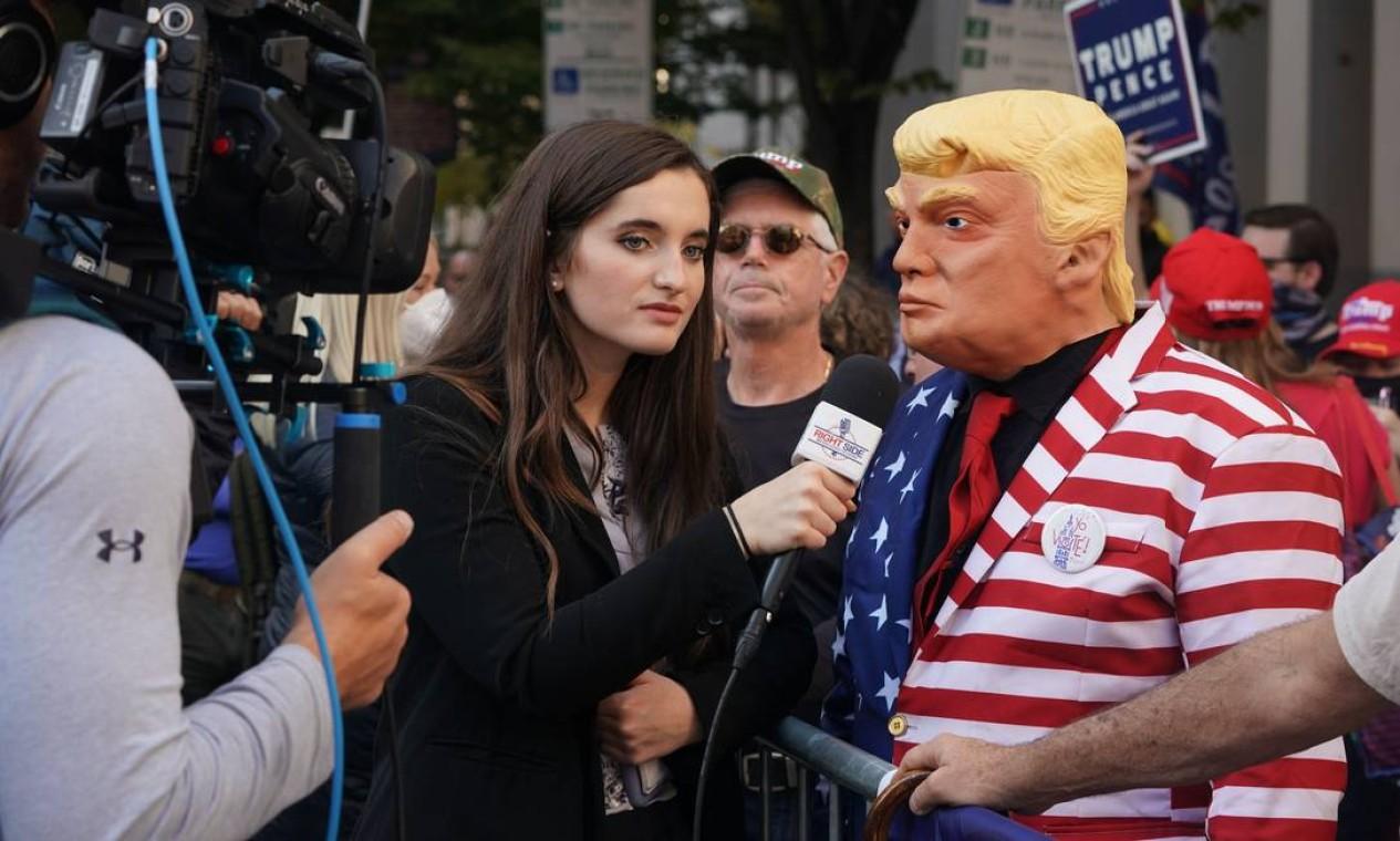 Apoiador vestido como o presidente dos EUA, Donald Trump, é entrevistado por um repórter de televisão do lado de fora do Centro de Convenções da Pensilvânia Foto: BRYAN R. SMITH / AFP