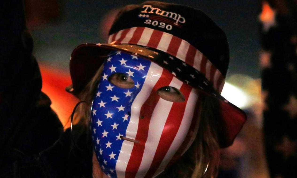 Um apoiador de Trump usa uma máscara e se junta à multidão contra a votação de Nevada, fora do Departamento Eleitoral do Condado de Clark Foto: RONDA CHURCHILL / AFP