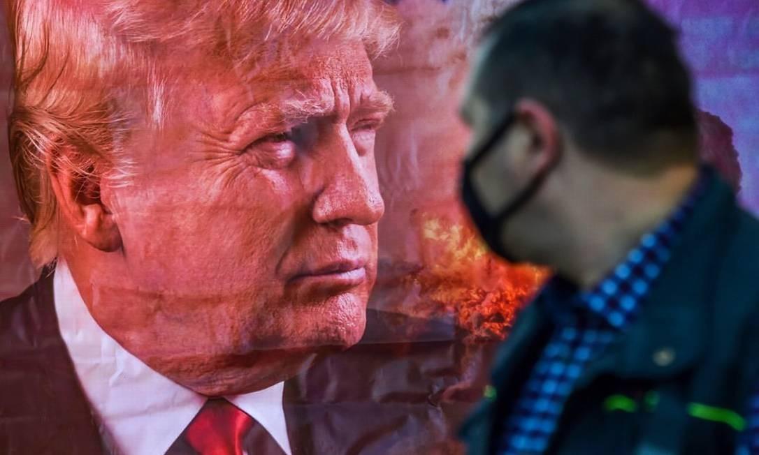 Homem observa cartaz com o rosto de Donald Trump Foto: VYACHESLAV OSELEDKO / AFP