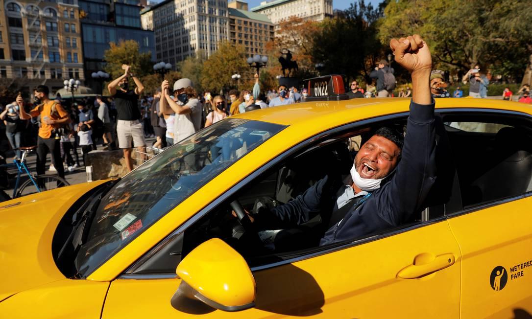 Taxista ergue o punho e grita enquanto pessoas comemoram o anúncio da vitória do candidato democrata, Joe Biden, em Manhattan, Nova York Foto: ANDREW KELLY / REUTERS