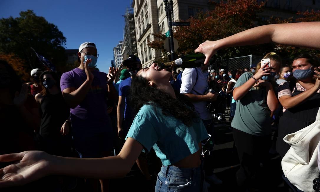 Apoiadores de Joe Biden celebram no Black Lives Matter Plaza, em Washington, após anúncio da vitória do democrata neste sábado Foto: HANNAH MCKAY / REUTERS