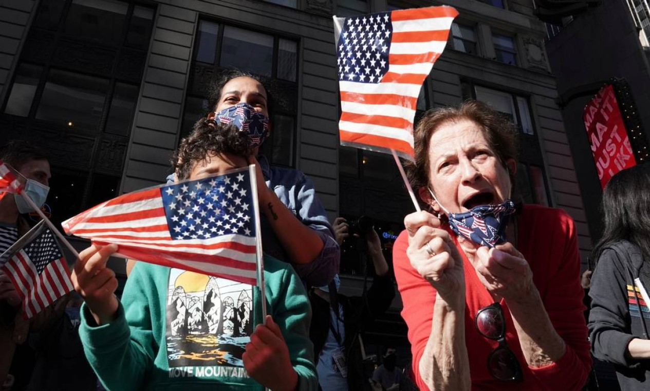 Pessoas festejam a vitória do democrata, na Times Square, em Nova York. Biden foi dado como vitorioso após assegurar sua vantagem no estado da Pensilvânia, somando 273 votos no Colégio Eleitoral Foto: CARLO ALLEGRI / REUTERS