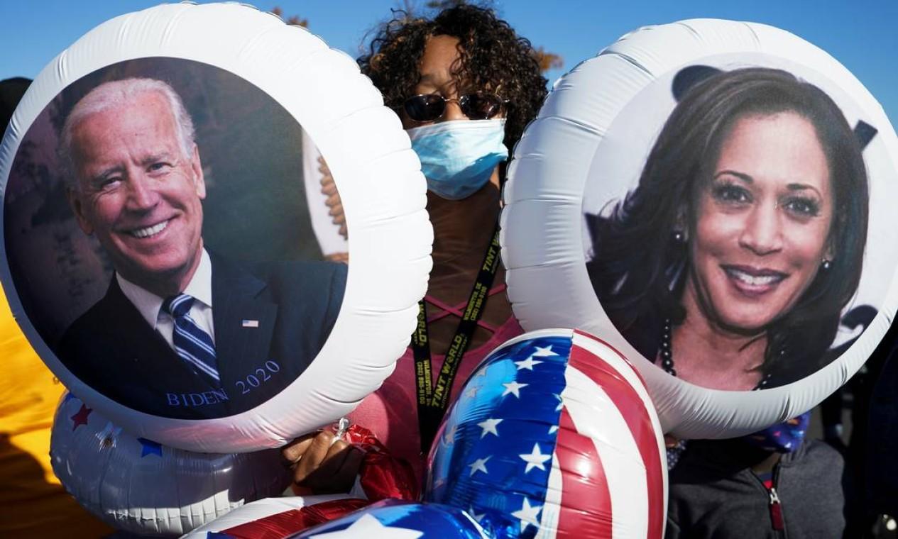 Em Wilmington, Delaware, partidária segura balões com os rostos de Biden e da vice, Kamala Harris, primeira mulher eleita para o posto nos EUA Foto: KEVIN LAMARQUE / REUTERS