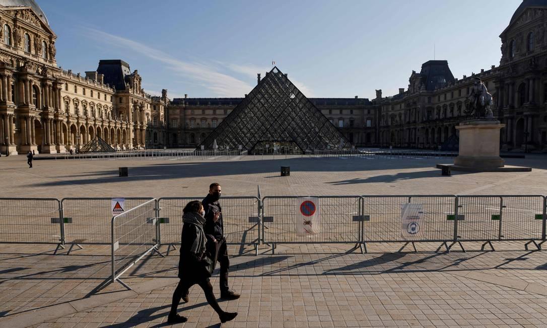 Casal caminha em frente ao Museu do Louvre, em Paris, durante o lockdown imposto pelas autoridades com a segunda onda da Covid-19 na região Foto: LUDOVIC MARIN / AFP