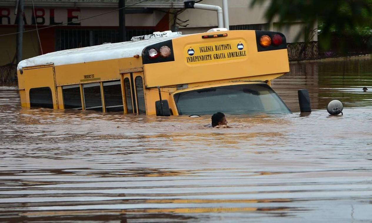 Pessoas nadam próximo a um ônibus em uma rua inundada em Omonita, município de El Progreso, departamento de Yoro, Honduras Foto: ORLANDO SIERRA / AFP
