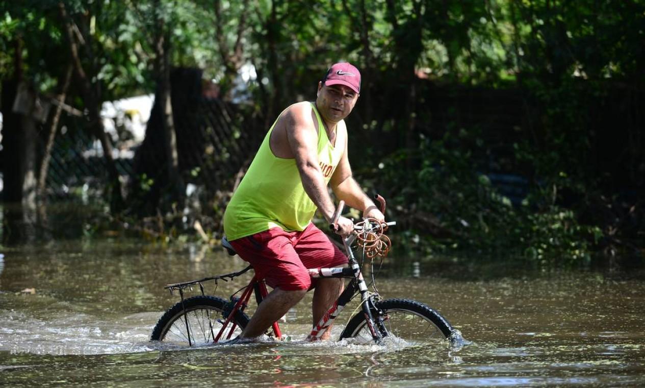 Homem anda de bicicleta ao longo de uma área inundada no município de Baracoa, departamento de Cortes, Honduras Foto: ORLANDO SIERRA / AFP
