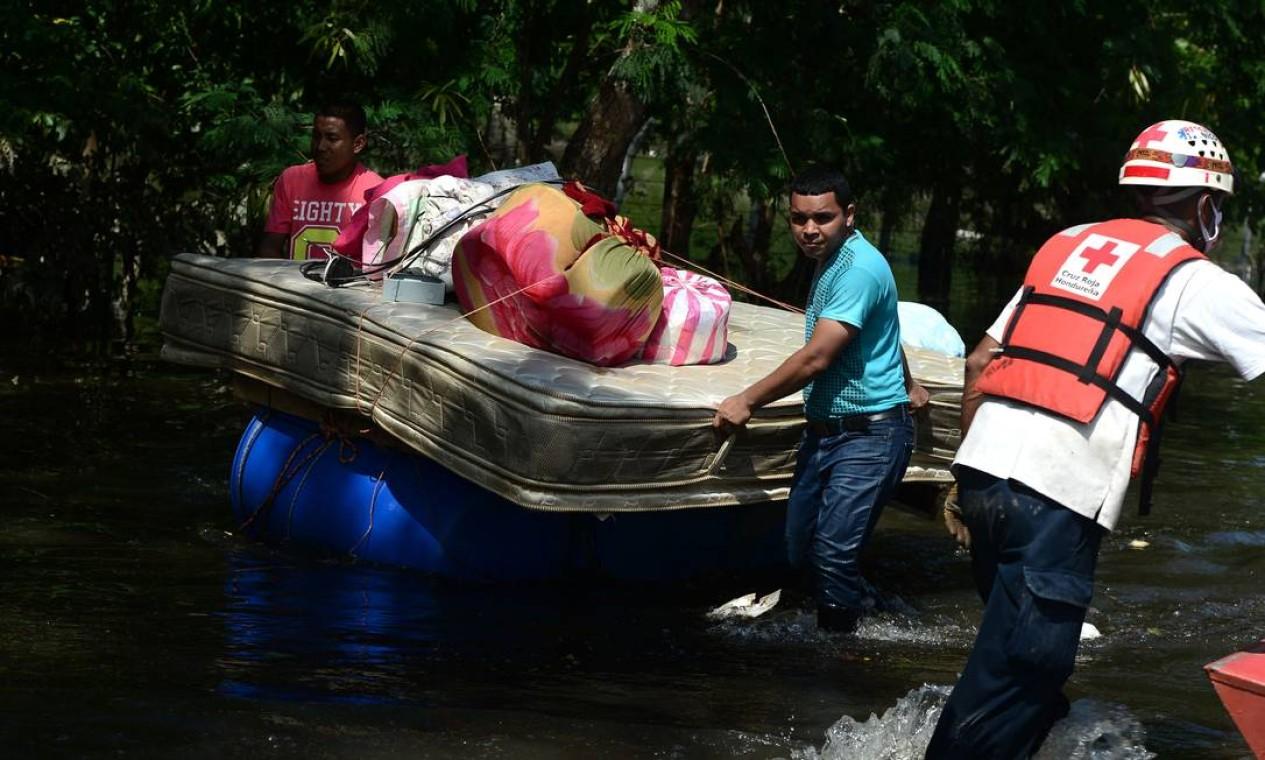 Residentes locais evacuam uma área inundada no município de Baracoa, departamento de Cortes, Honduras, em 8 de novembro de 2020. - Dezenas de pessoas morreram ou permanecem desaparecidas enquanto os restos do furacão Eta desencadearam enchentes e deslizamentos de terra em sua marcha mortal América Central. (Foto de Orlando SIERRA / AFP) Foto: ORLANDO SIERRA / AFP