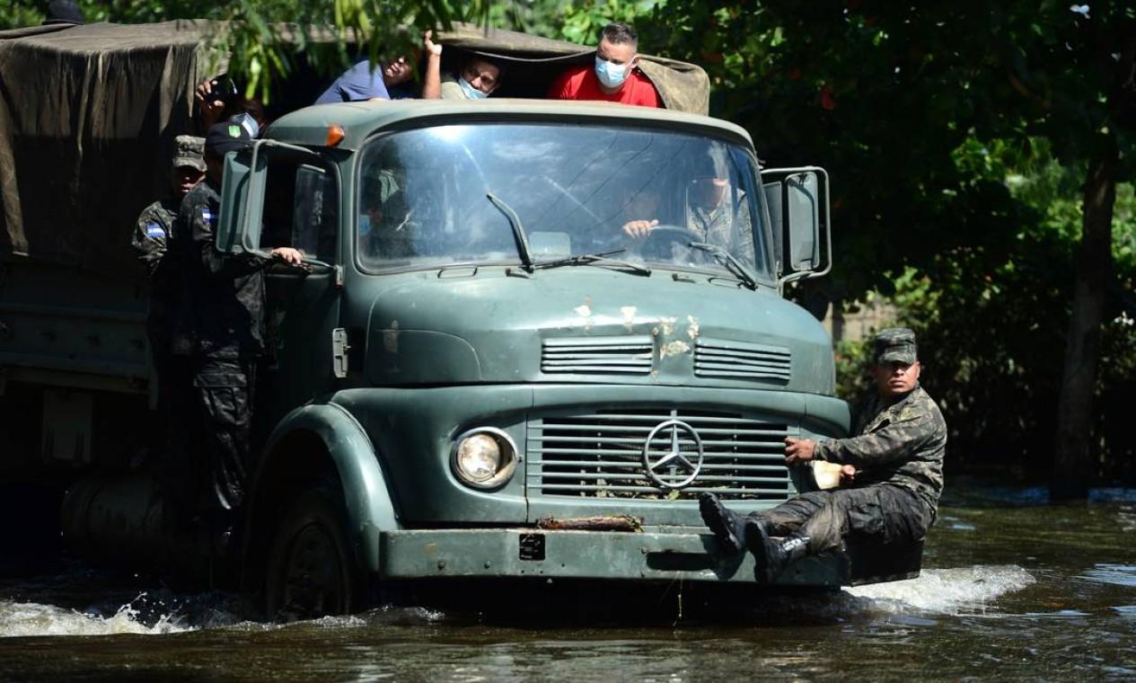 TOPSHOT - Soldados de Honduras evacuam residentes locais de uma área inundada no município de Baracoa, departamento de Cortes, Honduras Foto: ORLANDO SIERRA / AFP