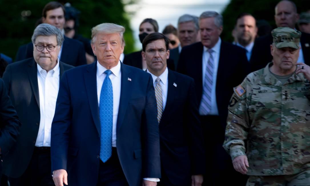 Mark Esper (C), atrás de Donald Trump na imagem, durante visita a uma igreja de Washington em junho de 2020 Foto: BRENDAN SMIALOWSKI / AFP
