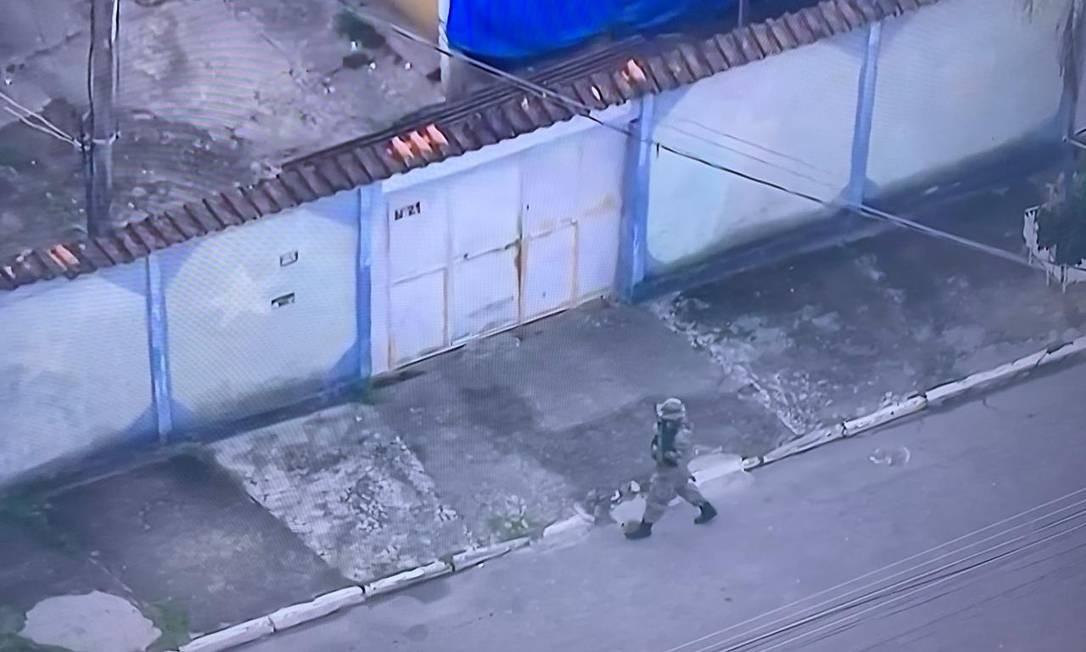Policial armado faz buscas pelas ruas de Jardim Gramacho em operação contra crimes ambientais Foto: Reprodução/TV Globo