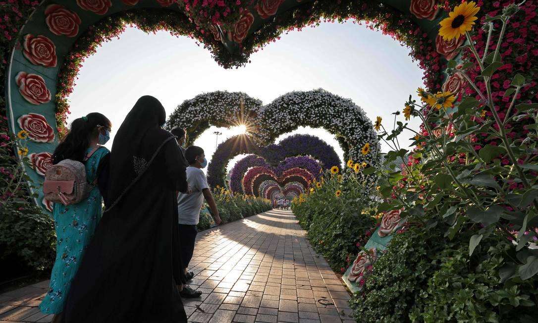 Visitantes caminham sob um arco de flores em forma de coração no Dubai Miracle Garden (Jardim dos Milagres de Dubai), o maior jardim de flores do mundo, nos Emirados Árabes Unidos Foto: GIUSEPPE CACACE / AFP