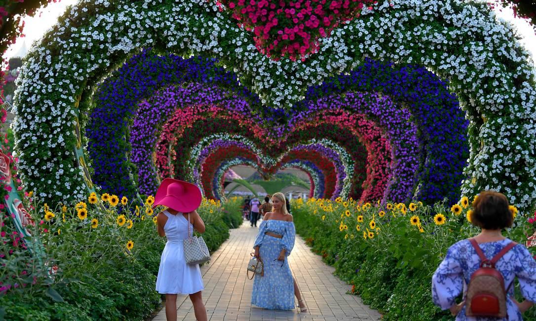 Uma mulher posa para uma foto em um túnel de flores em forma de coração Foto: KARIM SAHIB / AFP