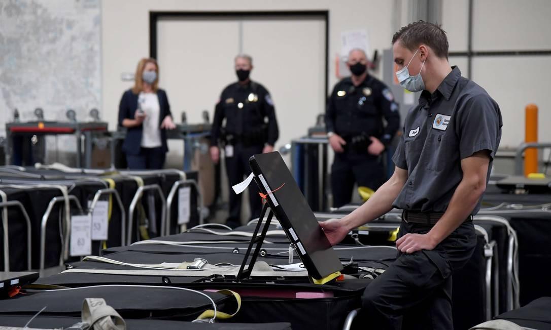 Funcionário do condado de Clark, em Nevada, inspeciona parte de uma urna eletrônica Foto: Ethan Miller / AFP