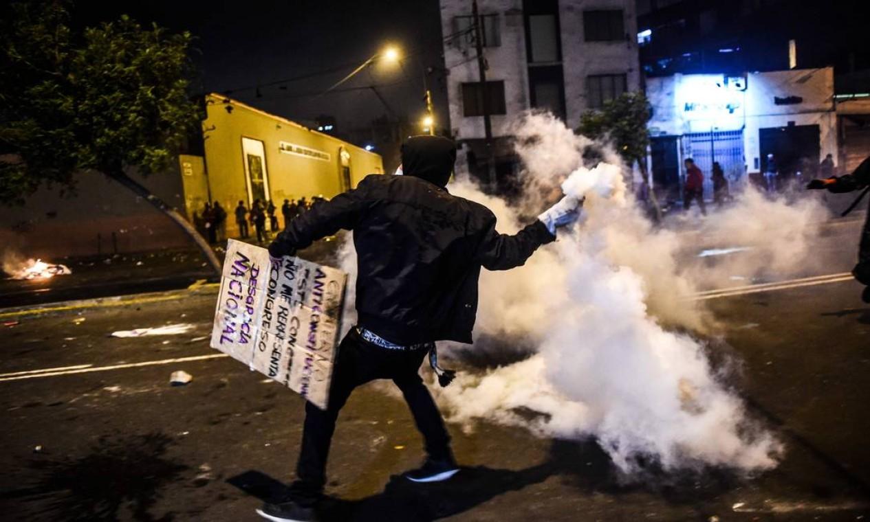 Manifestante atira bomba contra polícia de choque durante protesto na capital peruana Foto: ERNESTO BENAVIDES / AFP