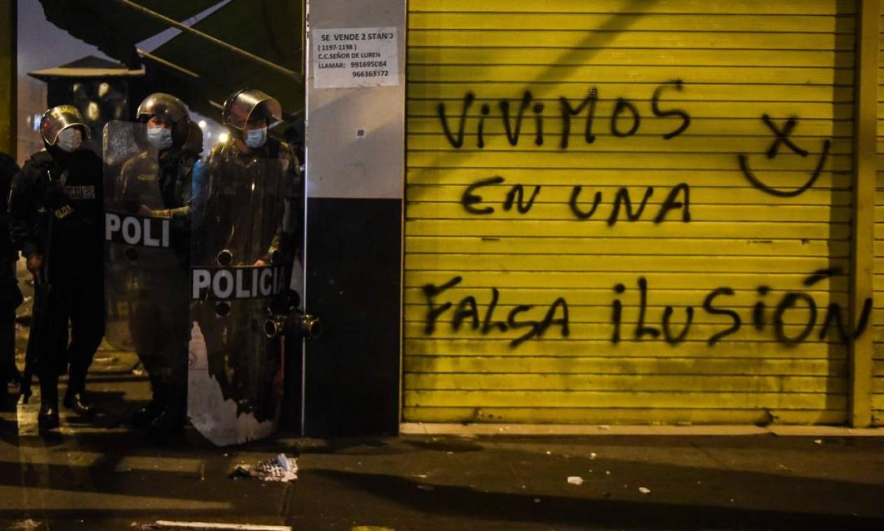 """Policiais se abrigam ao lado de loja fechada com a pichação na porta que diz: """"vivemos uma falsa ilusão"""". Foto: ERNESTO BENAVIDES / AFP"""