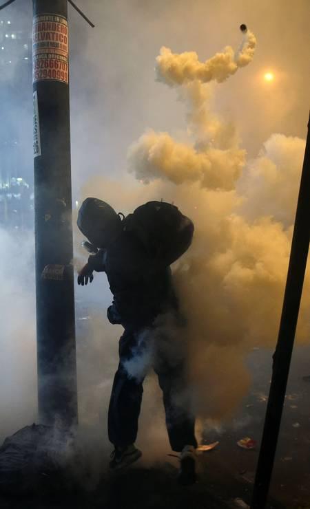 Manifestante atira bomba de gás contra policiais durante protestos na capital Lima Foto: ERNESTO BENAVIDES / AFP
