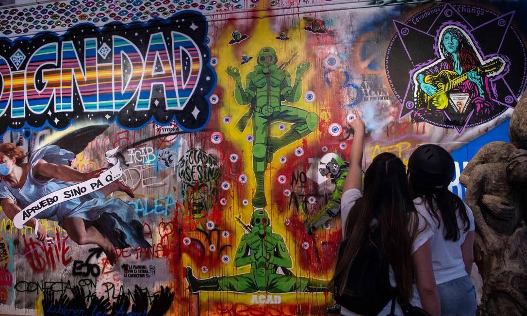 Visitantes observam peças de arte de rua relacionadas aos protestos contra o governo chileno de Sebastián Piñera Foto: MARTIN BERNETTI / AFP