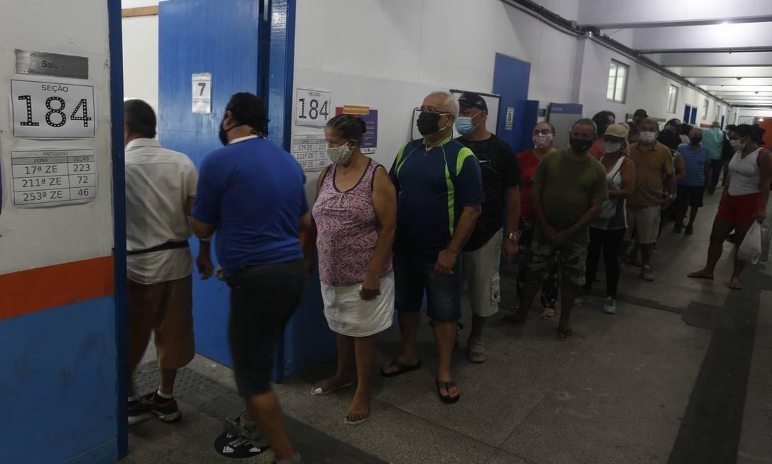 Primeiro turno das eleições municipais. De máscara, mas sem manter distanciamento, eleitores formam fila para votar no CIEP Ayrton Senna, na Rocinha Foto: Fabiano Rocha / Agência O Globo