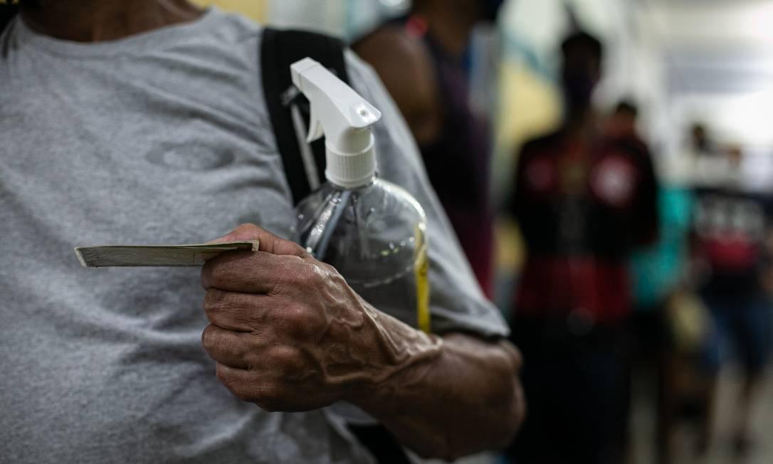 Eleitor próprio borrifador de álcool 70°, enquanto espera a vez de votar no Ciep Ayrton Senna Da Silva, Rocinha Foto: Hermes de Paula / Agência O Globo