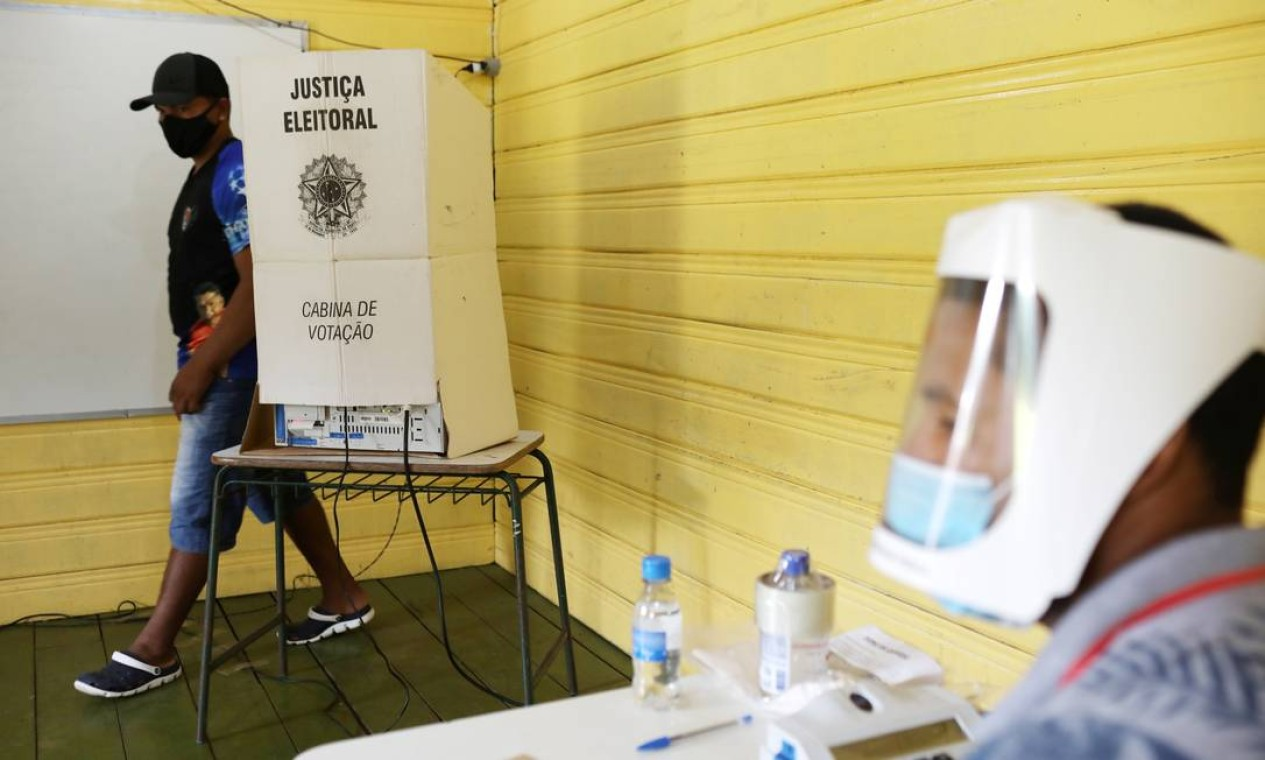 Um eleitor deixa cabine da urna após registrar seu voto em uma seção eleitoral às margens do Rio Negro, onde vivem ribeirinhos de comunidade conhecida como Catalão, no Amazonas. Medidas de segurança contra o coronavírus foram adotadas até nos locais mais remotos de votação Foto: BRUNO KELLY / REUTERS