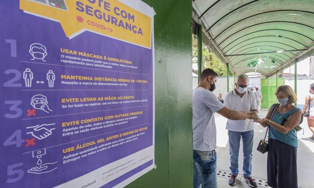 Voto com segurança: regras de ouro contra o coronavírus foram sinalizadas na Escola Estadual Senador Adolfo Gordo, em São Paulo. Aplicação de álcool em gel na entrada do local de votação Foto: Edilson Dantas / Agência O Globo