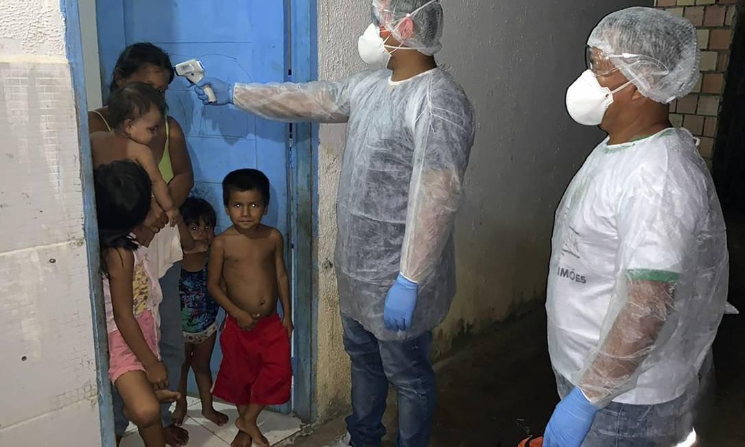 Profissionais de saúde medem temperatura de indígenas Tikuna em Lago Grande, Amazonas, em exame realizado durante pandemia do coronavírus Foto: AFP