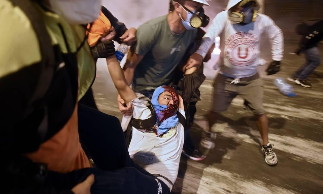 Manifestante peruano é carregado por colegas durante protesto Foto: ERNESTO BENAVIDES / AFP - 14/11/2020