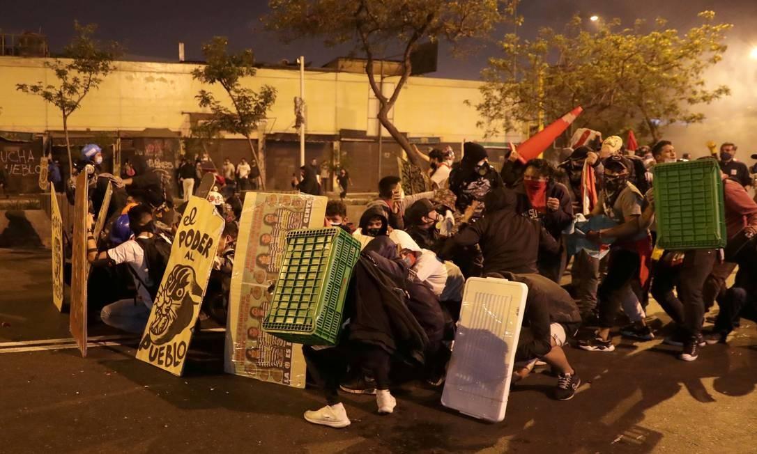 Manifestantes improvisam proteção contra disparos da polícia de choque Foto: SEBASTIAN CASTANEDA / REUTERS - 14/11/2020