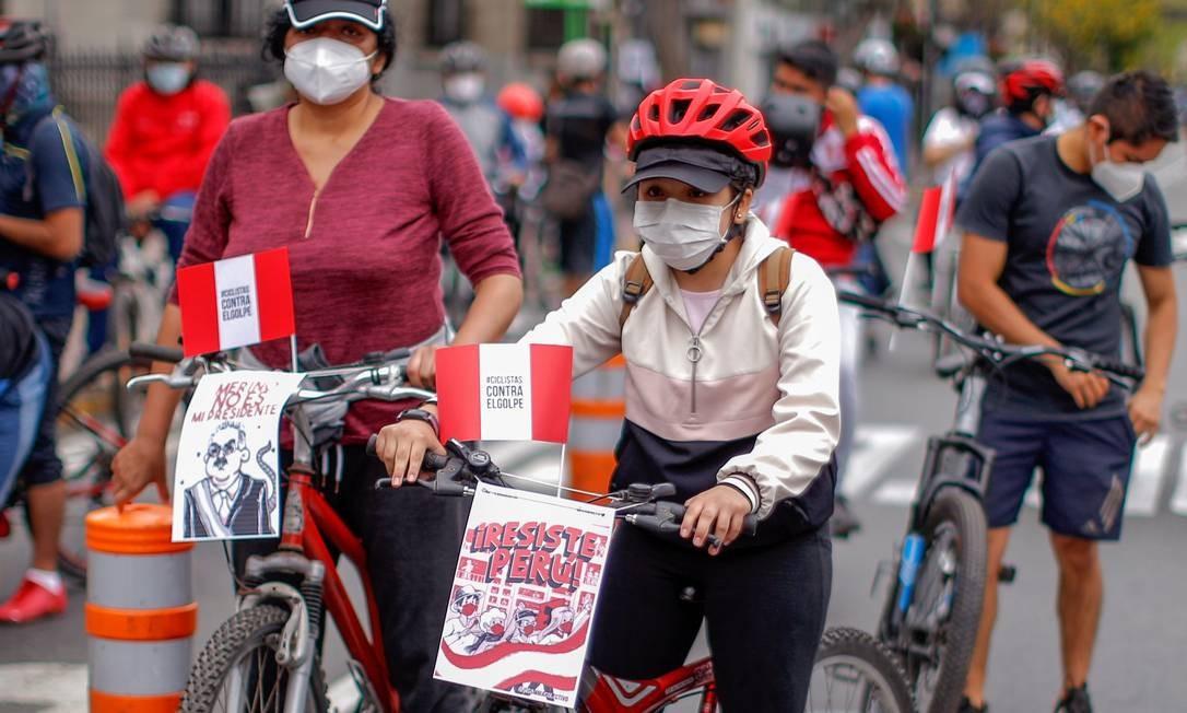 """Manifestantes de bicicelta carregam cartazes contra o governo interino: """"Merino não é meu presidente"""" e """"Peru resiste"""", dizem os cartazes Foto: LUKA GONZALES / AFP - 15/11/2020"""
