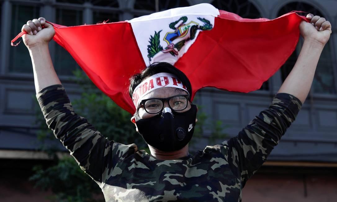 Manifestante comemora com bandeira do Peru a renúncia de Manuel Merino Foto: STRINGER / REUTERS - 15/11/2020