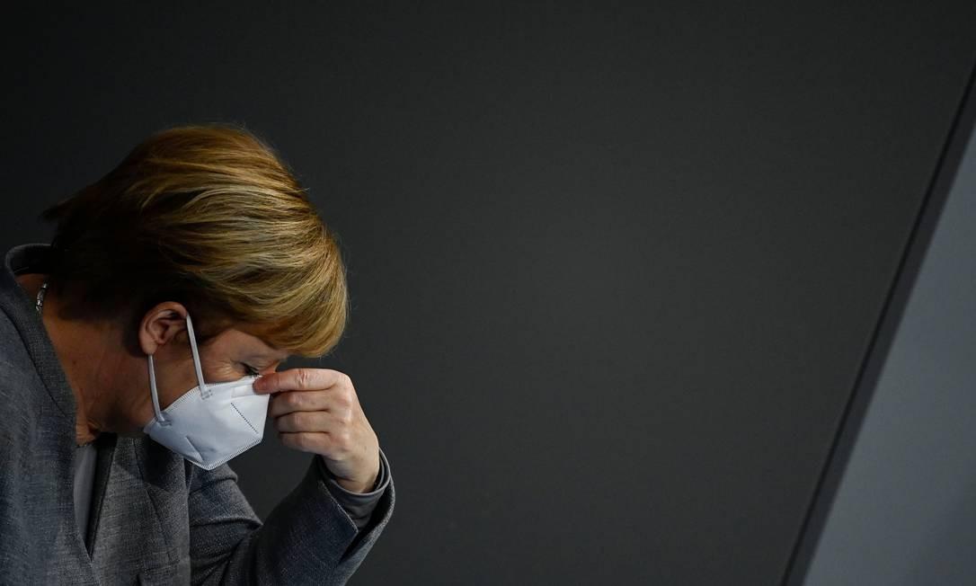 A chanceler alemã, Angela Merkel, ajusta sua máscara facial durante uma sessão no Bundestag sobre medidas para conter a disseminação do novo coronavírus Foto: TOBIAS SCHWARZ / AFP