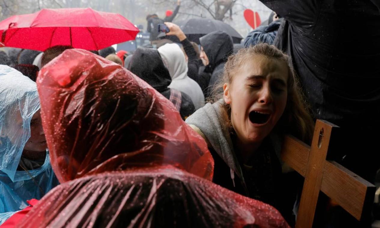 Jovem com um crucifixo chora enquanto a polícia usa um canhão de água para dispersar os manifestantes que protestam contra as medidas restritivas pelo governo alemão para limitar a disseminação do novo coronavírus Foto: ODD ANDERSEN / AFP - 18/11/2020
