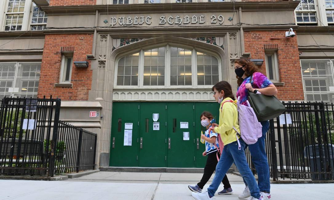 Crianças de máscaras vão para escola na cidade de Nova York, nos EUA Foto: ANGELA WEISS / AFP