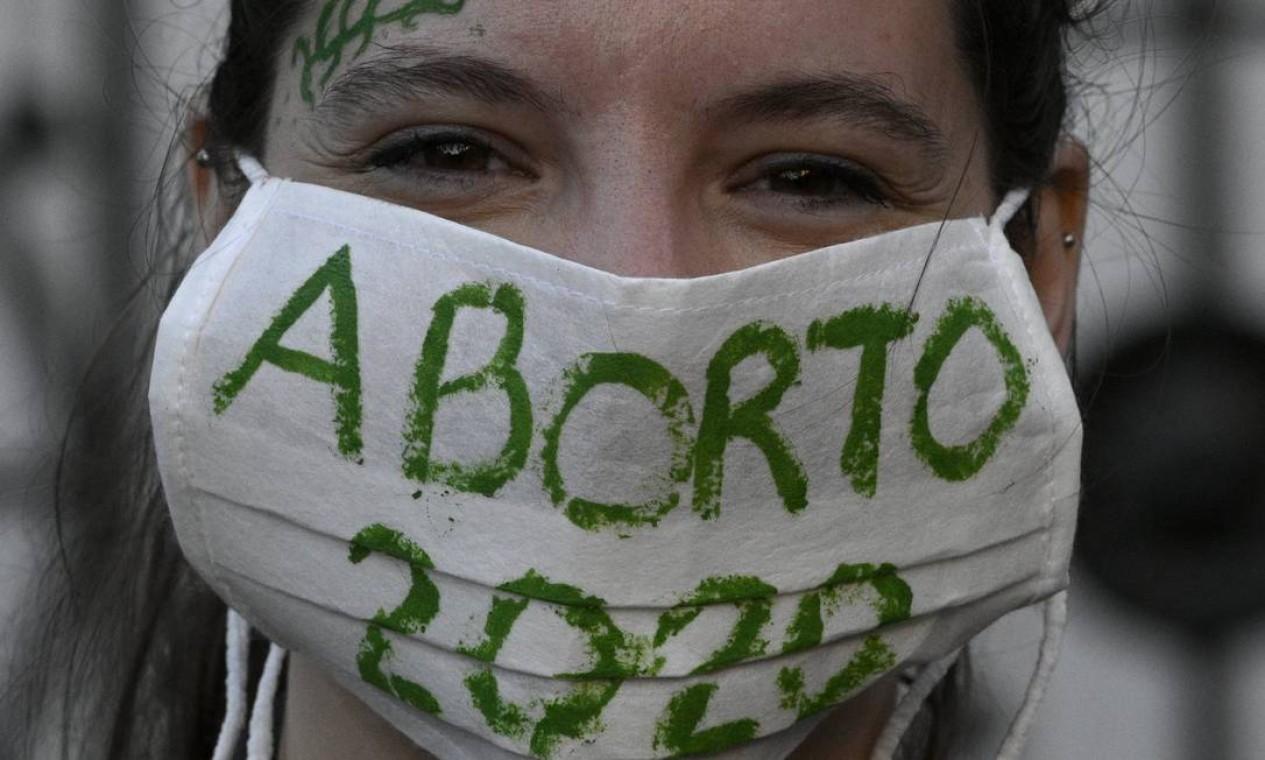 Um ativista usa uma máscara em manifestação em frente ao prédio do Congresso, em Buenos Aires Foto: JUAN MABROMATA / AFP