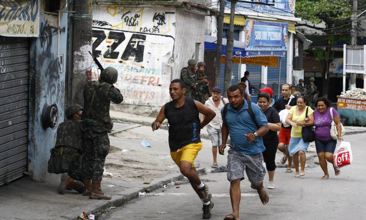 Moradores correm dos tiros durante a tomada do Complexo do Alemão Foto: Pablo Jacob / Agência O Globo - 26/11/2010