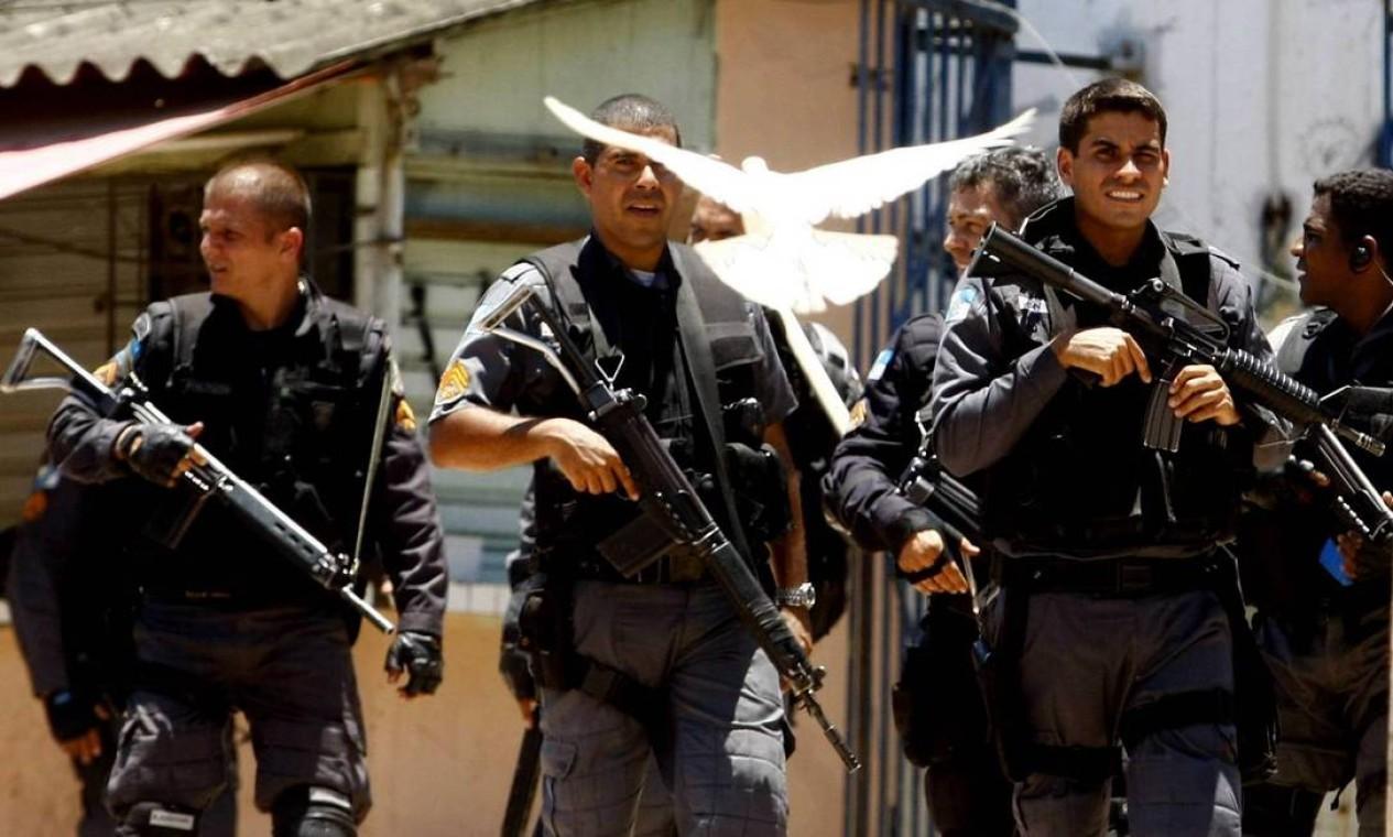 Pomba branca aparece diante de policiais militares fortemente armados Foto: Pablo Jacob / Pablo Jacob / Agência O Globo - 28/11/2010